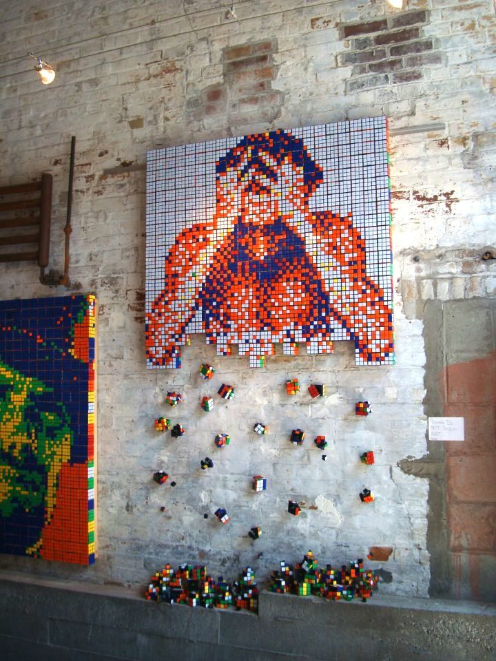 """Spectacular Rubik's Cube portrait of a man disintegrating...  First spotted at Morris Museum's new show, """"Toying with Art,"""" (in New Jersey) this incredibly intriguing portrait made out of Rubik's Cubes was also submitted as an entry into CubeWork's art contest in September 2012. Though we'd like to give the artist credit, we're not sure who the person is behind this piece."""