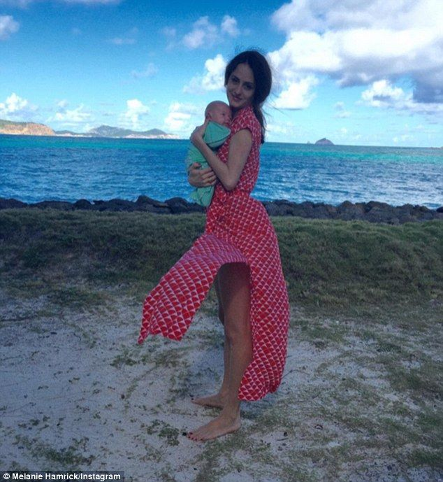 Sweet snap: Mick Jagger's partner Melanie Hamrick, 29, flaunted her slimmed down figure in a stylish dress as she cradled her newborn son Deveraux Octavian Basil while at the beach
