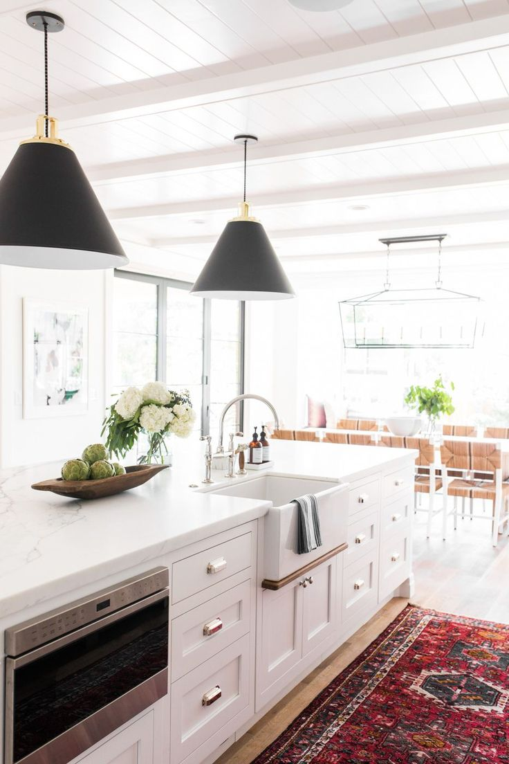 Modern farmhouse meets The Hamptons in Studio McGee's latest remodel || vintage kitchen rug, black cone pendants, marble counters, farmhouse sink, bridge faucet