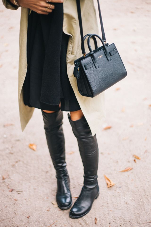 Jacey Duprie wearing a black dress and scarf from COS, trench coat from Hermes, boots from Stuart Weitzman and the bag is from Saint Laurent