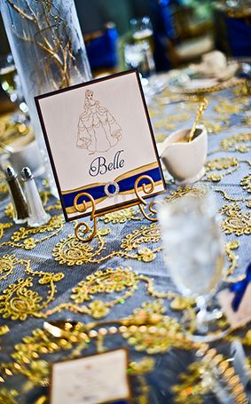 Disney royalty inspired gold and blue reception decor with Belle table card