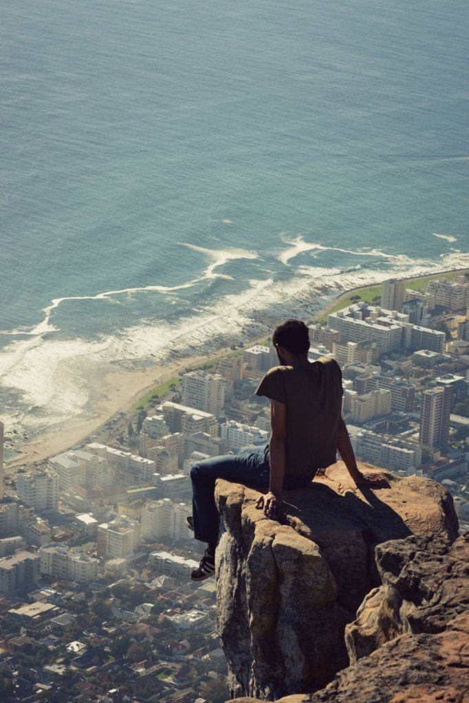 Looking Down from Lion's Head   Photograph by trottin-the-globe.tumblr.com   In this heart-stopping photograph we see a hiker overlooking Cape Town from Lion's Head, a mountain in Cape Town, South Africa, between Table Mountain and Signal Hill