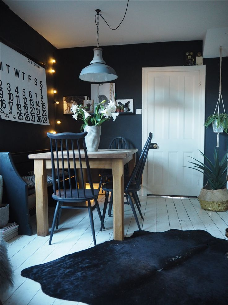 Monochrome dining room painted in Farrow and Ball off black with white painted wooden floorboards and Stendig calendar.
