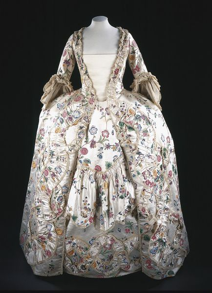This elegant robe and petticoat are fine examples of a woman's formal daywear in the early 1760s. In cut, fabric and design they were the height of fashion. The pattern on the silk is hand-painted. The fabric was first sized with alum to make the paint adhere. Next the design was drawn freehand in ink or silverpoint. A variety of pigments were used, including white lead or a chalk ground for the highlights.