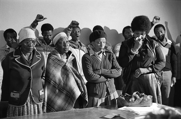 Pauline Moloise (mother of Ben), two women & Winnie Madikizela Mandela mourn at the Memorial Service for Benjamin Moloise, who was hanged earlier that morning. Khotso House, Johannesburg, October 18, 1985. © Gille de Vlieg.