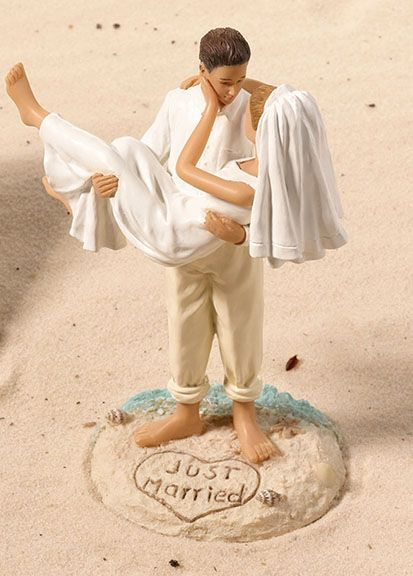 Sandy Beach Bride & Groom Cake Topper. Measuring 7 inches tall, this fun-filled cake figurine shows a groom carrying his bride on a sandy beach.