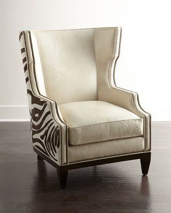 """Massoud Borra Hairhide Chair The perfect blend of simple and exotic, this modified wing chair combines creamy leather upholstery with exotic hairhide for a look that speaks volumes. Poplar frame. Leather upholstery. Made from natural materials; no two are exactly alike. Unique variations in each hide add to the authentic look. Nailhead trim. Mortise-and-tenon construction. 36""""W x 42""""D x 44""""T. Seat, 22""""W x 25""""D x 19""""T; arms, 25""""T."""
