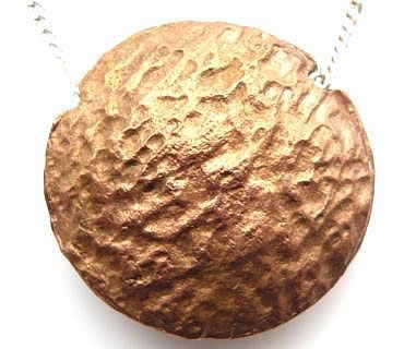 Copper lentil pendant which has a different pattern on the other side.