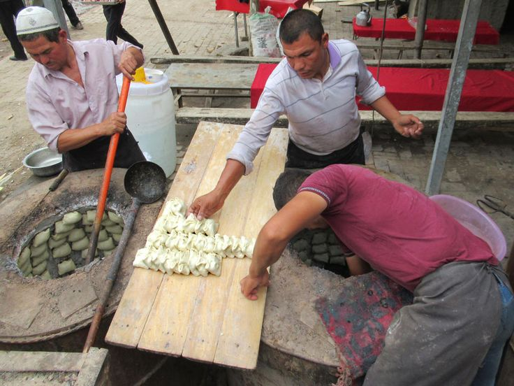 Dough punchers at the Sunday livestock market in a suburb northwest of Kashgar, Xinjiang, China, use underground ovens to bake their buns.