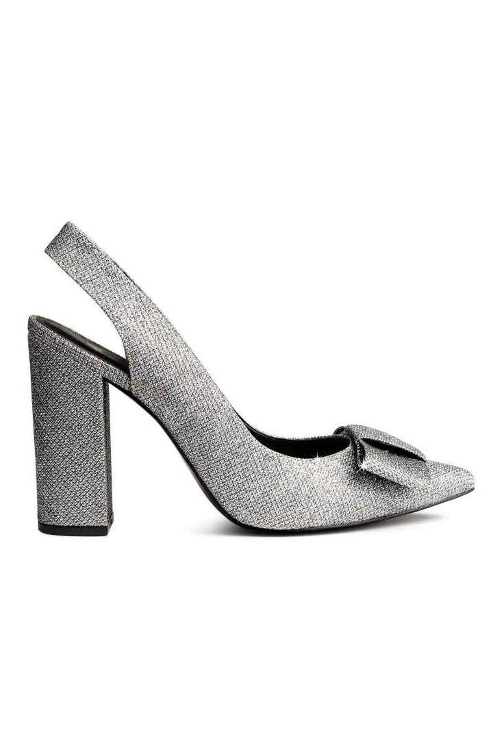 Sapatos clássicos brilhantes: Sapatos clássicos altos em pele sintética brilhante. Modelo com biqueira fina, laço decorativo na frente e tira no calcanhar com elástico no interior. Saltos forrados. Forro e palmilhas em pele sintética. Solas de borracha. Salto de 11,5 cm.