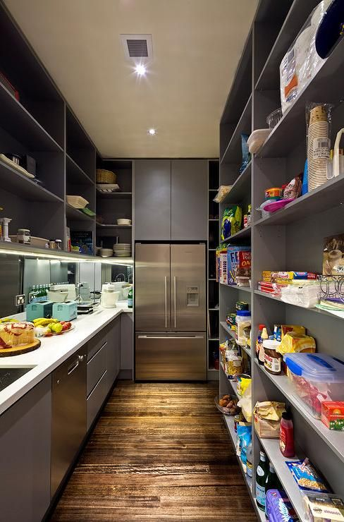 Contemporary gray pantry features a wall of floor to ceiling shelves facing gray cabinets topped with white quartz fitted with a sink next to a stainless steel dishwasher.