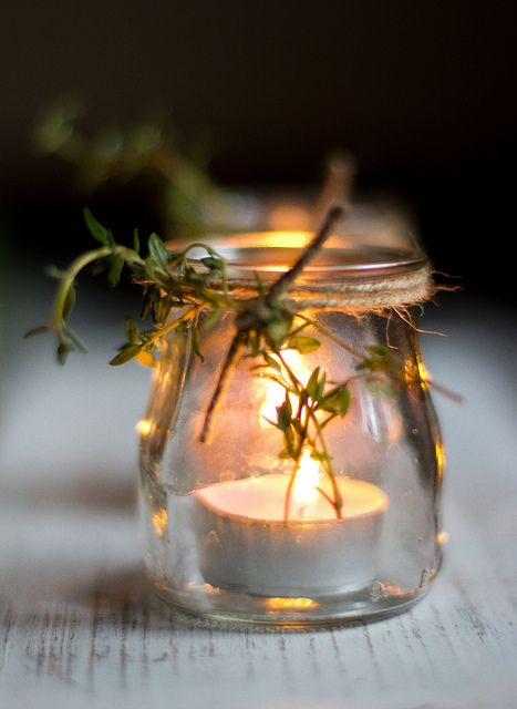 Light in simple glass pot with thyme twig and twine. Maybe six or more in a row on the dinnertable outside.