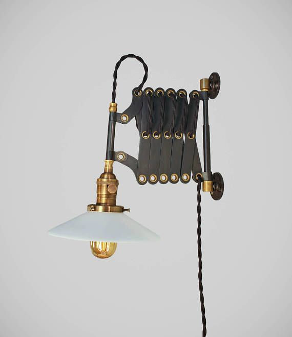 This is a more ramped up version of our standard scissor sconce. Based on the originals from the 1940s and constructed of durable materials: solid steel body with brass hollow rivets and cast iron wall mounts. All parts have been hand-aged for vintage effect. Subtle variations to the finish on the black steel body and one extra set of scissor links.  Comes wired with an antique style lamp socket, 9 feet of twisted cloth cord, and an industrial wall plug. The scissor arm opens and closes…