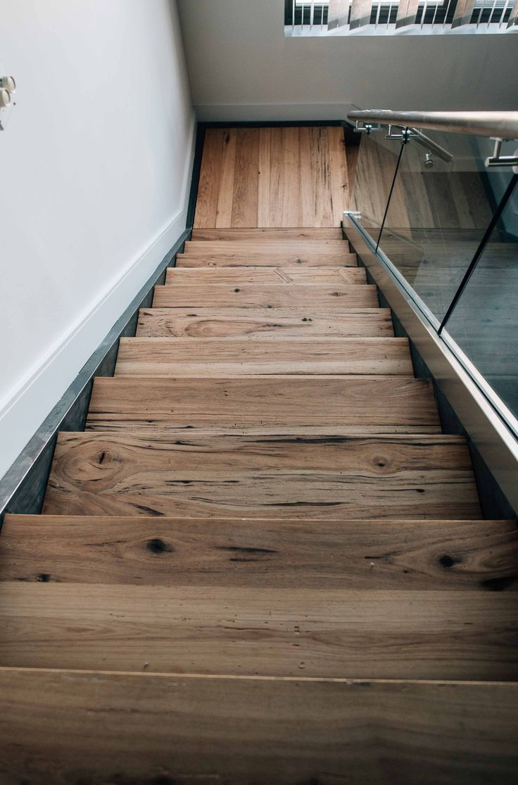 This handsome staircase utilizes a perfect combination of glass, raw steel  and reclaimed hickory. The 2 thick treads were finished in place in thi