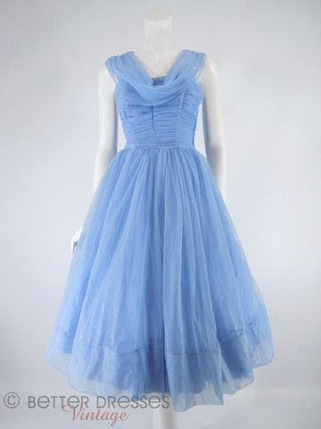 Dreamy 1950s party dress in periwinkle blue. Ruched, boned bodice with feminine draping at front and watteau train at back. Nipped waist. Full skirt to wear with or without a crinoline (not included).