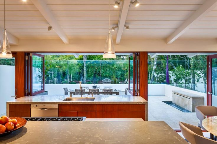 Limestone waterfall-style countertops frame custom mahogany cabinetry in the sleek, modern kitchen. The tongue-and-groove ceiling is original to the 1950s midcentury home but given a fresh coat of white paint and lit with track lighting.