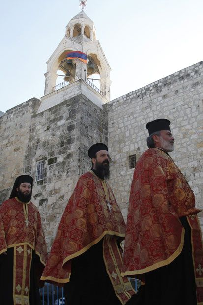 Christian  Orthodox priests take part in a procession in Bethlehem's Manger Square outside the Church of the Nativity