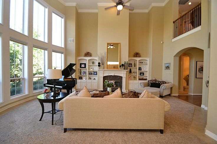 2 Story Livingroom With Built Ins Around Fireplace Featuring Two Story High Ceilings