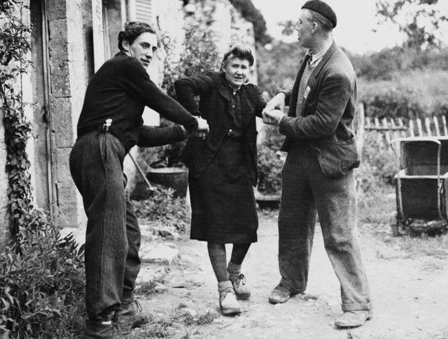 Two French patriots drag Grande Guillotte from her home in Normandy, France on July 10, 1944. After she was discovered to be collaboration with the enemy
