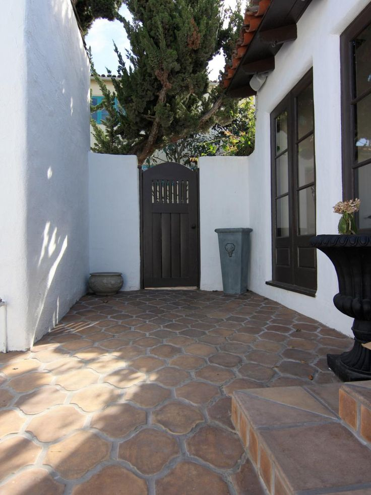 This Spanish-style kitchen courtyard forms an arresting study in contrasts. Terra-cotta-toned concrete pavers and red barrel roof tiles appear richer against pristine white walls, which in turn look luminous against the dark door and window casings.