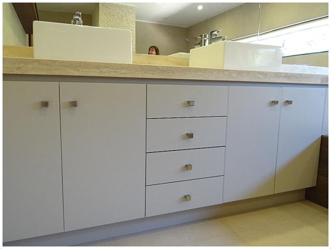Mueble lavamanos con cubierta de mármol empotrado sobre jacuzzi. Tiradores de metal satinado