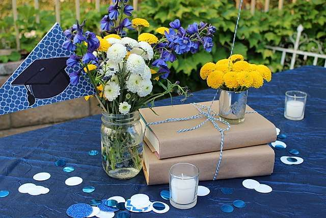 TABLE TOPPERS—This book idea is super cute and on trend with the graduation theme. It also is super cost efficient. Who doesn't have an abundance of old books laying around? Visit your local grocery store for the paper bags.