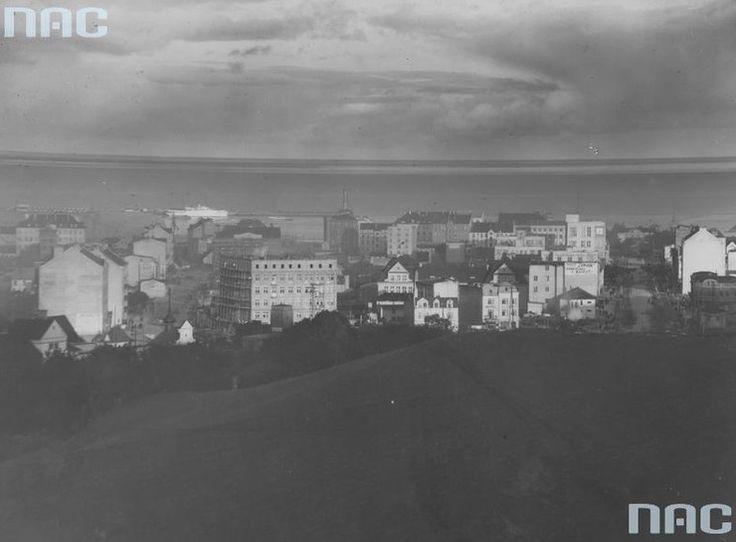 Panorama Gdyni. Widoczny budynek motelu, szyld maszyn do szycia Singer i czekolady Wedel. Rok 1930 Prężny rozwój miasta zatrzymała II wojna światowa. I choć Gdynia nie została zniszczona tak jak Gdańsk czy Warszawa, to poniosła ogromne straty w ludności. Większość polskich mieszkańców została przez Niemców wysiedlona lub trafiła do obozów koncentracyjnych, wielu poległo na frontach. Do wyzwolonego w marcu 1945 roku miasta szybko zaczęli powracać rodowici gdynianie, przybywali warszawiacy…