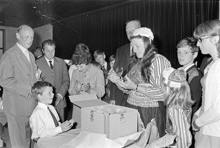 """Ter gelegenheid van de viering van het 150-jarig bestaan van de Bondsspaarbanken werd aan 20 gezinnen een """"gezinsgeschenk"""" aangeboden op het hoofdkantoor van de Spaarbank voor de Stad Amsterdam. Moeder Teerhuis uit Marken krijgt een feestdronk ingeschonken door de Onder-Directeur, de heer NICO M.A. TER WOLBEEK, onder toezicht van de voorzitter van de Raad van Toezicht, JHR. MR. E.W. ROELL."""