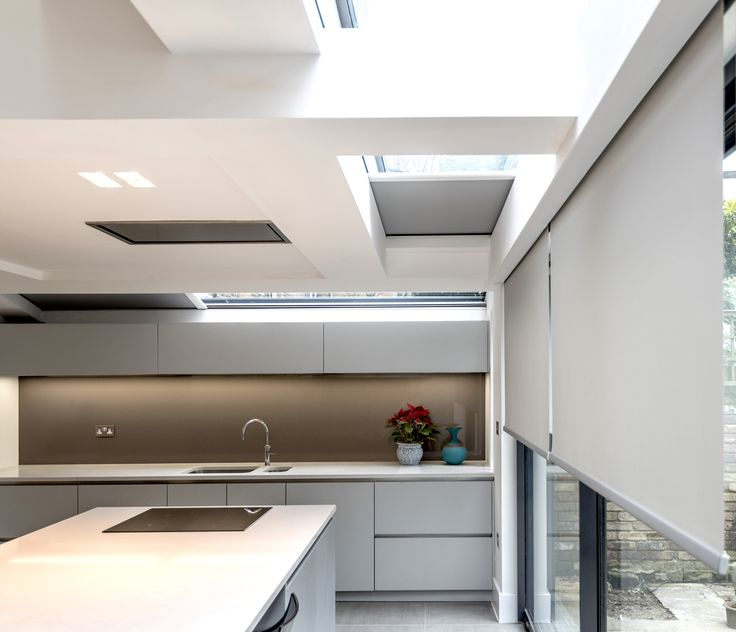 Recessed roller shades in contemporary kitchen. Minimalist design with blinds not visible when not in use.