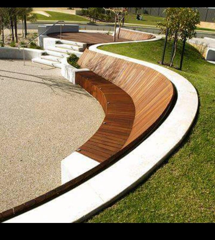 Curved retaining wall to slopping lawn of