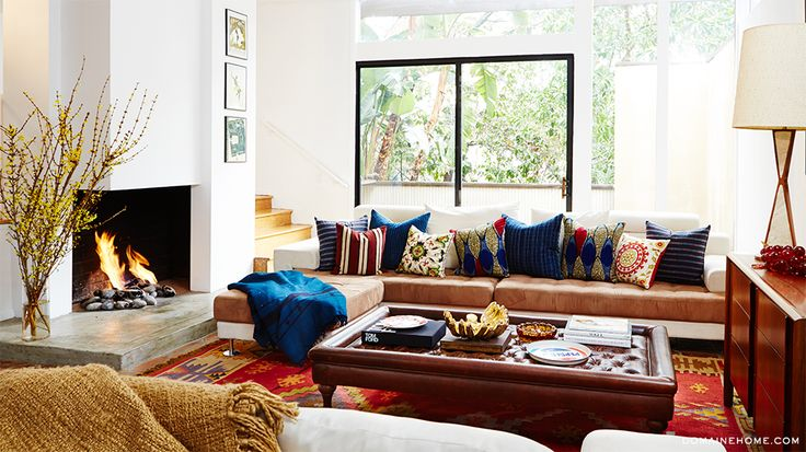 Layering lots of pillows on a tired sofa works to cover, distract and even style the room well.  Love the tall branches next to the fireplace too as a trend. #stagingtips #stagingtrends