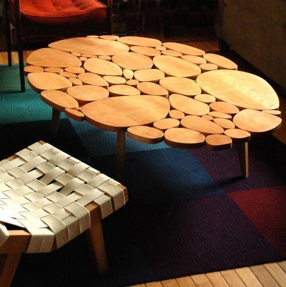 Деревянный овальный стол из пропиленных стволов деревьев.