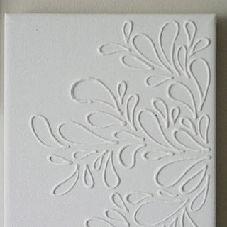 Elmer's glue on canvas. Then paint the whole thing one color. Love it! Great idea to make several in coordinating colors to place above bed as a headboard!