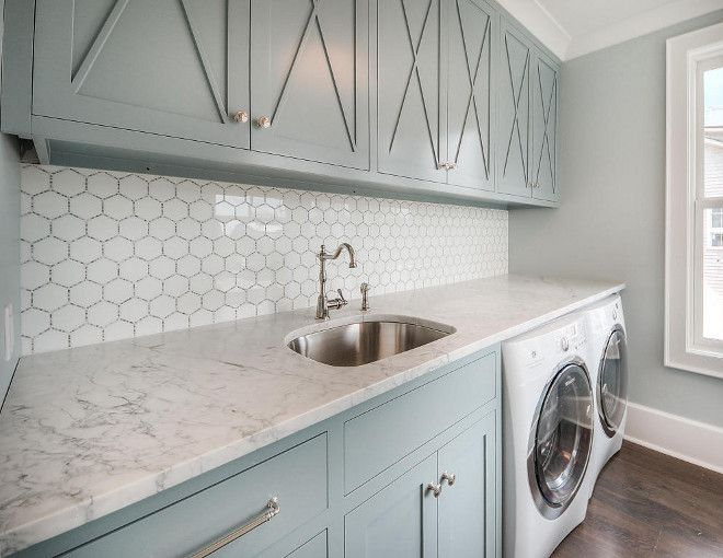 Laundry room with light green cabinets and marble countertops