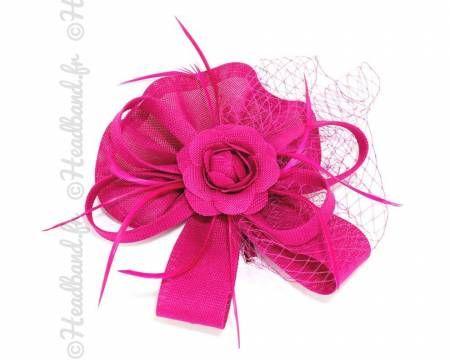 Bibi à cheveux rose fushia en sisal pourvu d'une décoration en forme de fleur, d'une voilette et d'une cascade de plumes. Avec une pince crocodile en métal pour pouvoir le fixer dans vos cheveux. A compléter avec une magnifique pochette de soirée ou des escarpins plutôt sobres.