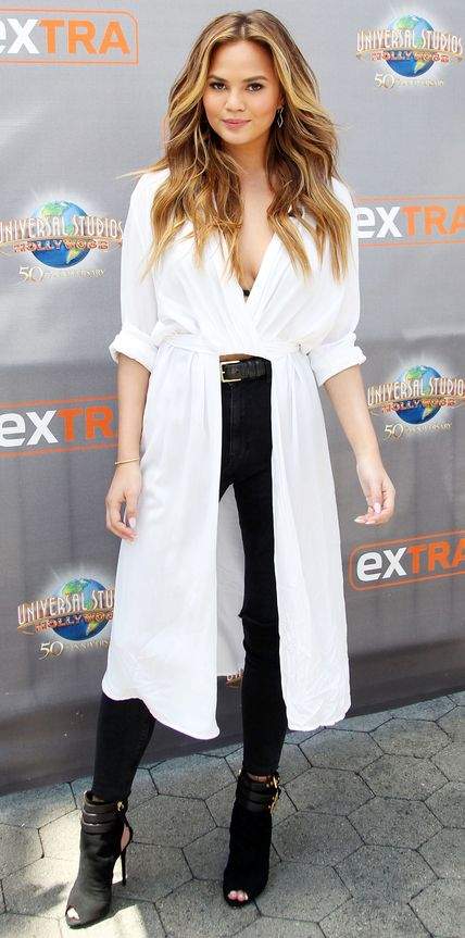 Chrissy Teigen made a statement on the set of Extra in a crisp white draped shirt dress that revealed black skinnies underneath. Her shoe of choice? Black suede Giuseppe Zanotti open-toe booties.