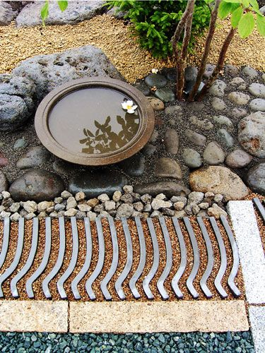 .Japanese style garden. paths of different materials, patterns, small pool with floating flower, reflection.