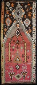 Very interesting small yoruk nomad prayer kilim using variations in weaving technique, colour and tribal motifs to produce a charming work of art. Unusual double prayer niche with upper diamond found in yoruk prayer kilims. Elibelinde hands on hips goddess, S hook and inner running meander borders, star and earing motifs. A womans prayer kilim woven as a dowry gift. About 50 years old in very good condition. Wool on hand spun brown sheep wool warp. 132x60cm No. 0017 €295