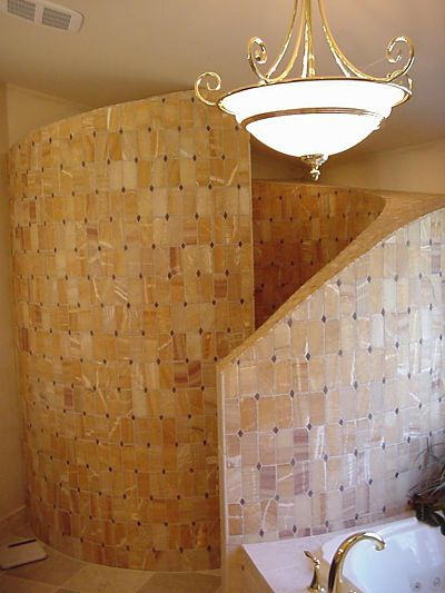 A curved tiled wall provides privacy for a walk-in shower without doors. By Neal's Design Remodel.