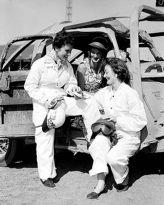 Female stock car motor racing drivers Miss A. McCarthy, Mrs M. Coglan and Miss M. O'Brien, share a cigarette at the Sydney Showground. November 22, 1955.