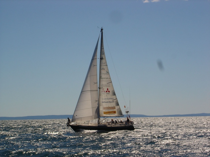 Now how about this cool shot - from our second vessel out across the water we see Frodo with full sail, big waves and a rider on the pulpit. Its a comfortable ride because we are reaching downwind. In the background is Isle Royale.