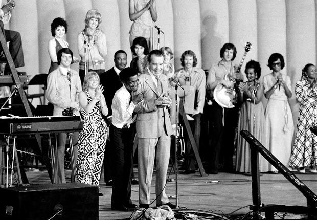 "1972 ELECTION - During a live television broadcast from a youth rally at the GOP CONVENTION in Miami Beach, PRESIDENT RICHARD NIXON finds himself on the receiving end of an enthusiastic embrace from entertainer SAMMY DAVIS, JR., who calls Nixon ""the president and the future president of the United States of America.""  Nixon's awkwardness makes the image instantly famous."