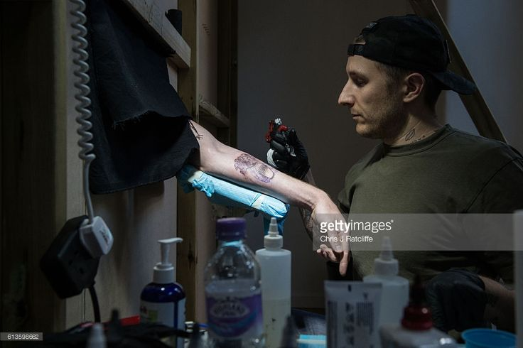 Cameron Ward, 24, has his first ever tattoo through a hole in the wall at celebrity tattoo artist Scott Campbell's event 'Whole Glory' on October 9, 2016 in London, England. The recipient sits on a chair with their arm through the wall as Scott Campbell tattoos on the other side of the wall. Campbell's tattoos usually cost thousands of dollars but at his event he gives members of the public free tattoos to stick their arm through the wall with no communication allowing Campbell to tattoo…