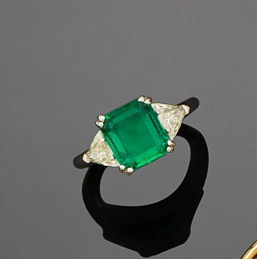 BOUCHERON Bague en or gris 750 millièmes, ornée au centre d'une émeraude rectangulaire à pans coupés, entre deux diamants triangulaires. Signée (sur le ressort). Tour de doigt : 54,5 (ressort) ; Poids… - Audap-Mirabaud - 10/06/2016
