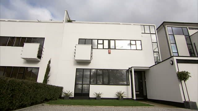 A white facade with black trim characterizes an Art Deco building on Rayners Lane in London. Available in HD.