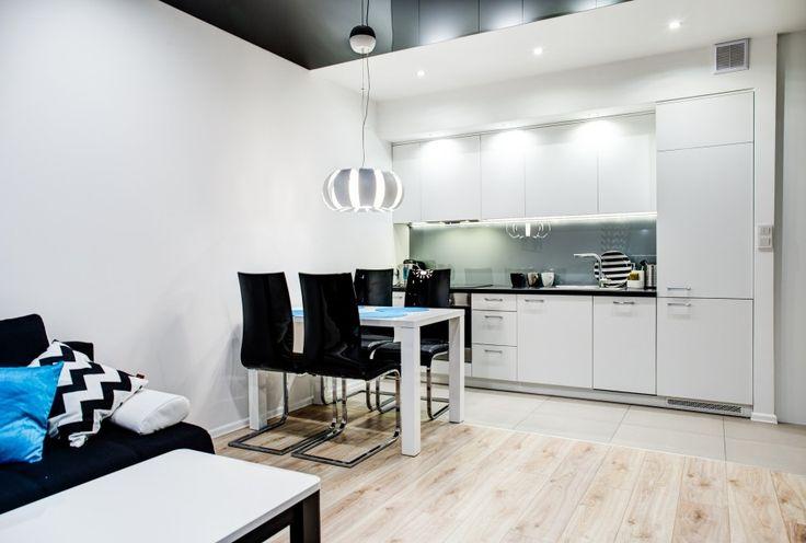 Aneks kuchenny w klasycznym stylu, a zarazem z nutką nowoczesności. Białe matowe meble z halogenowym oświetleniem idealnie wpisują się w klimat mieszkania.