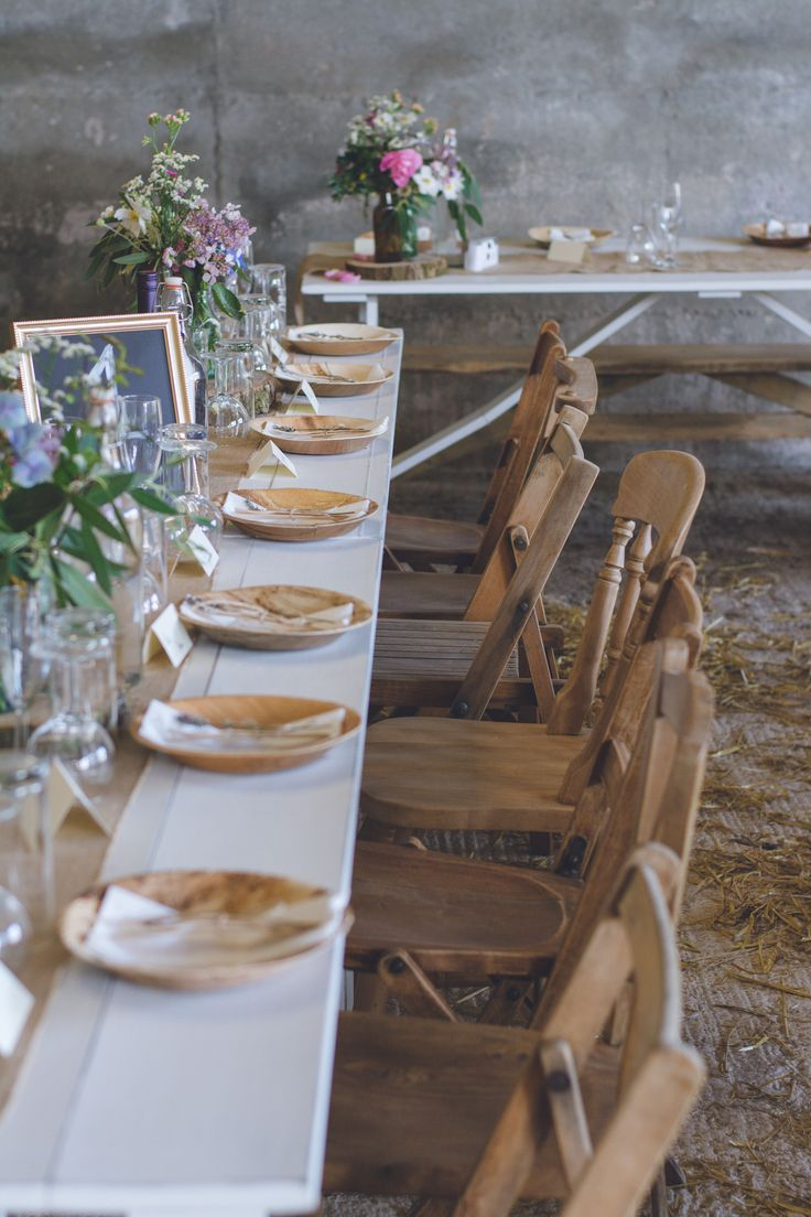 Our vintage wooden chairs set up with our white distressed trestle table for a rustic barn wedding in Cornwall