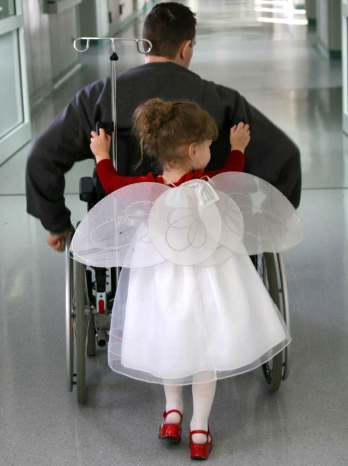 child pushing wounded warrior in a wheelchair