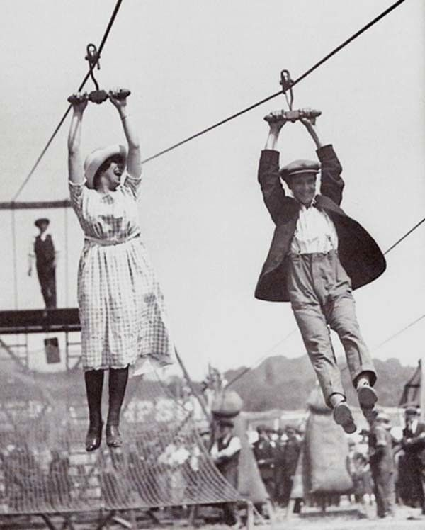 A couple enjoys an old-fashioned zipline at a fair (1923).