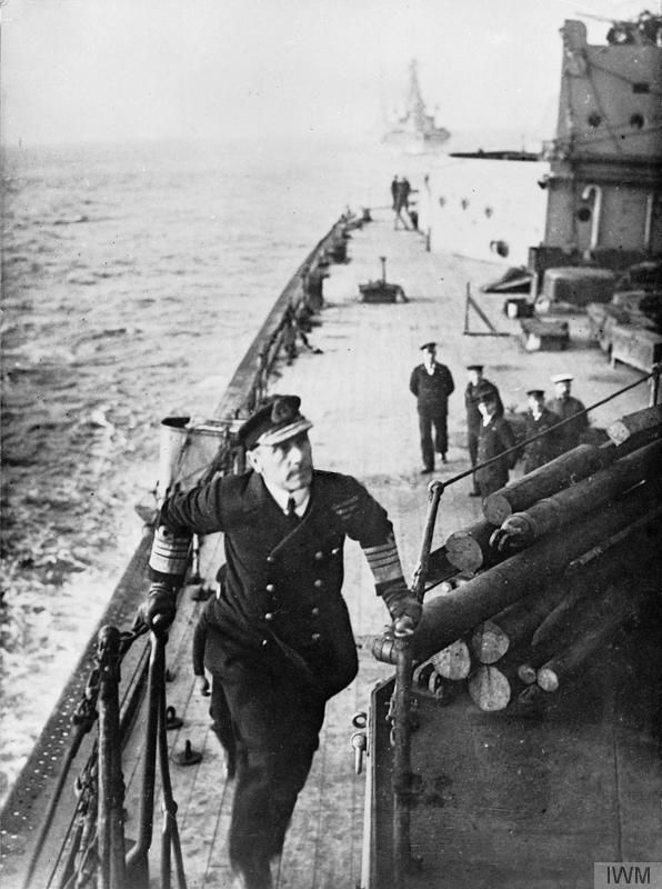 THE BATTLE OF JUTLAND 31 MAY 1916. Admiral Sir John Jellicoe, Commander in Chief of the Grand Fleet, reaching the top of a flight of steps on board a battleship. A small group of sailors is stood below looking up at him whilst a capital ship sails astern of the ship.